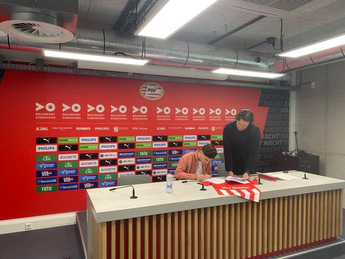 Arnhemmer Yaël Gil y Muiños (16)  tekent zijn driejarig contract bij PSV, onder toeziend oog van  PSV's hoofd opleidingen Ernest Faber.