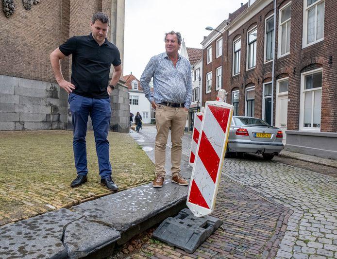 Mark van den Bos (links) van Stichting Monumenten Bezit beoordeelt de schade aan de eeuwenoude stoep voor de Oostkerk. De brokstukken zijn voorlopig even recht gelegd tot definitieve reparatie. Rechts Oostkerkdirecteur Leo Hannewijk.