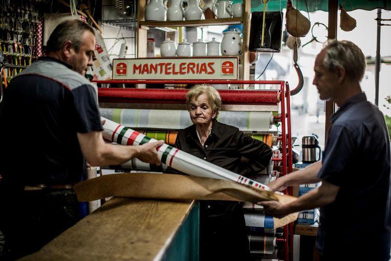 Aguirre koopt een toile cirée in Gernika. De man van de verkoopster werd ook ooit als vluchteling opgevangen in België. Beeld Diego Franssens
