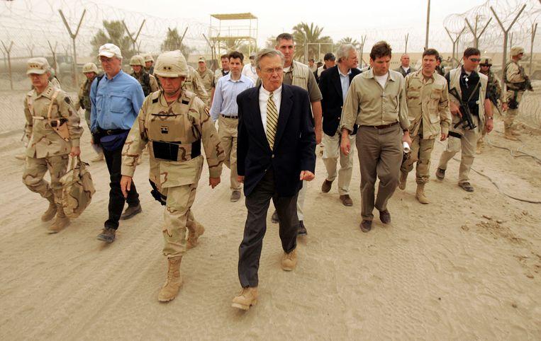Toenmalig minister van Defensie Donald Rumsfeld tijdens een bezoek aan de beruchte Abu Ghraib-gevangenis nabij Baghdad in 2004.  Beeld AFP