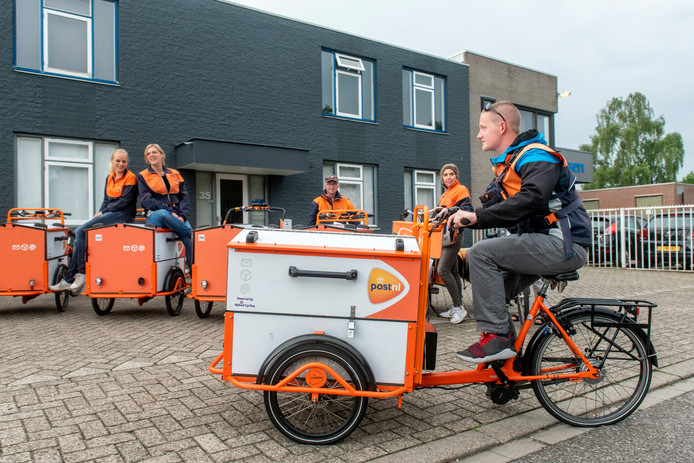 Een bezorger van PostNL rijdt weg op zijn elektrische bakfiets.