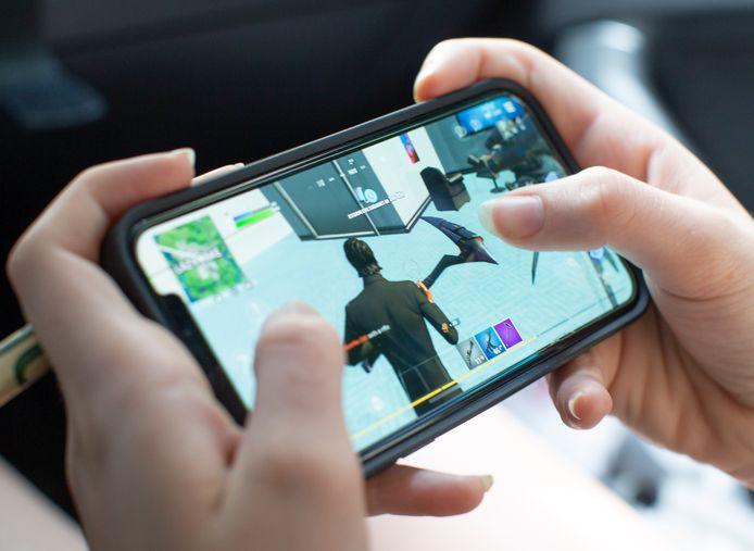 Een tienermeisje speelt het populaire Fortnite op haar iPhone.