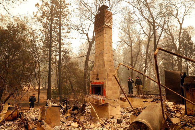 Een schoorsteen is het enige wat rest van een gebouw in Paradise, stellen politieagenten vast.  Beeld Photo News