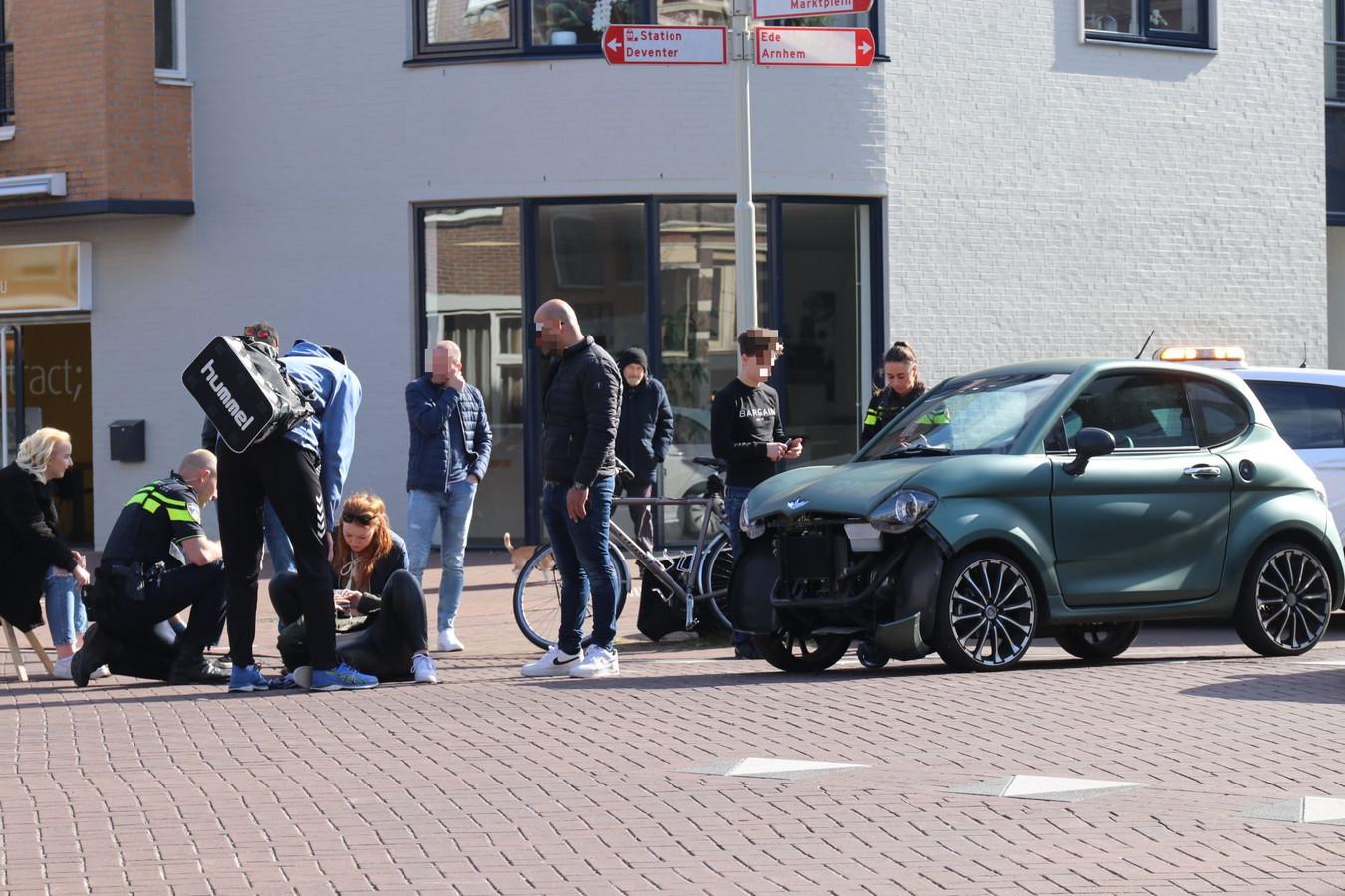 Het meisje op de scooter ligt op straat en wordt geholpen door omstanders.