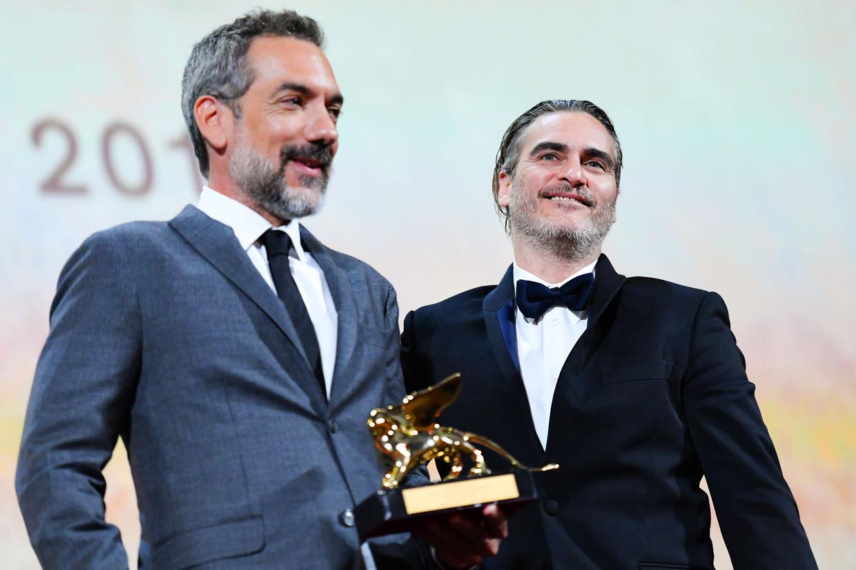 Regisseur Todd Phillips (l.) en hoofdrolspeler Joaquin Phoenix nemen de Gouden Leeuw voor 'Joker' in ontvangst. Beeld AFP