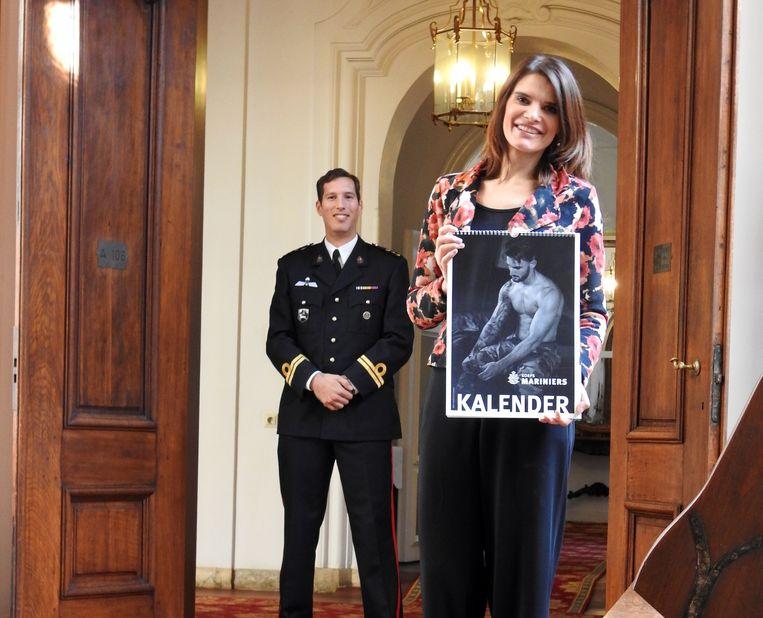 Staatssecretaris Barbara Visser van Defensie heeft het eerste exemplaar van de marinierskalender gekregen uit handen van marinier Maurits Holle. Beeld Bas Bosscher/Ministerie van Defensie