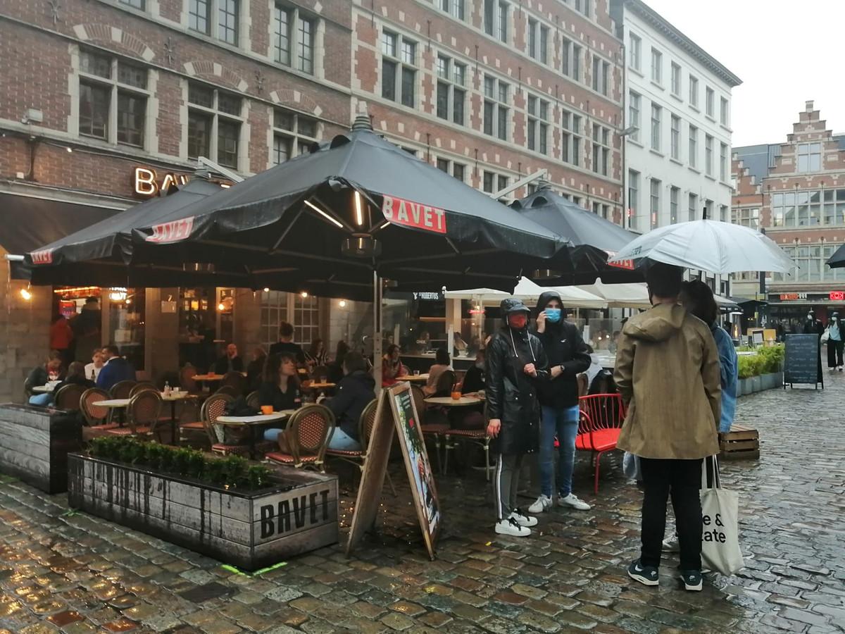 Hier en daar schoven mensen onder een paraplu aan, voor een overdekt plekje op het terras.