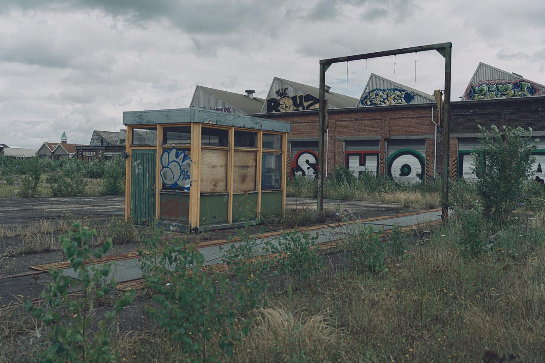 De oude werkplaats ligt er al een tijd verloederd bij: ramen zijn kapotgeslagen en gevels staan vol graffiti.  Beeld Wouter Van Vooren