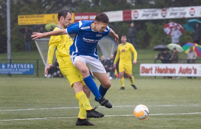Aron Veldhuizen (blauw shirt) wordt van achteren belaagd door Martijn Aveskamp van VRC.