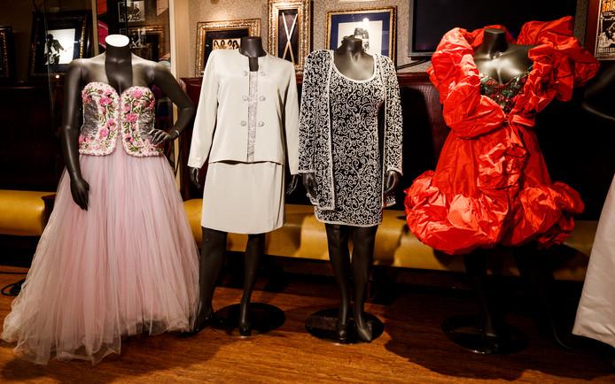 Links de roze jurk die voor 10.000 dollar van de hand ging, rechts de rode jurk die 7500 dollar opbracht.