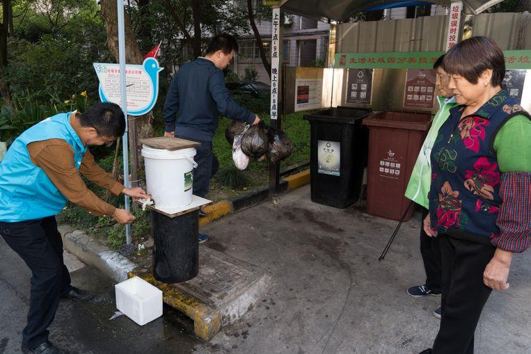 Vrijwilliger Niu Guangcheng (l.) helpt zijn buren met het sorteren van hun afval in de Huamei Tuinwijk in Shanghai. Beeld Ruben Lundgren