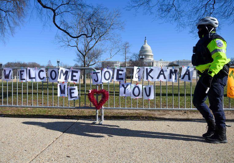 Op een hek bij het Capitool in Washington hebben aanhangers van de aankomende president Joe Biden en vicepresident Kamala Harris steunbetuigingen aangebracht. Beeld AFP
