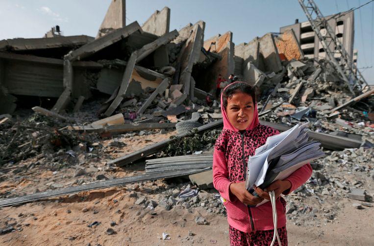 Een Palestijns meisje staat voor het puin van een gebouw dat werd vernietigd tijdens de Israëlische luchtaanvallen in Gaza-stad.  Beeld AFP