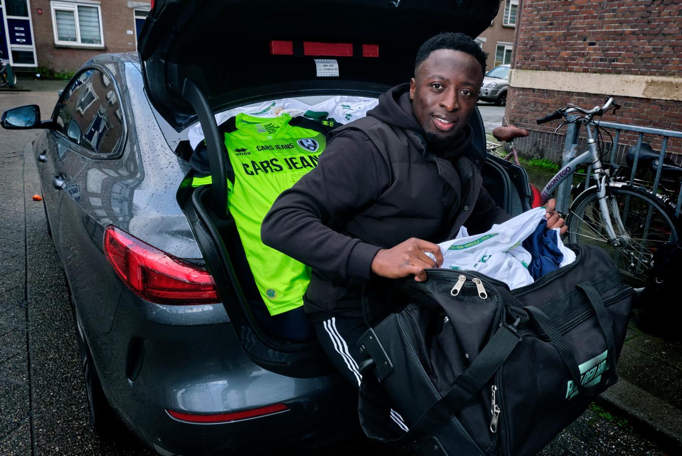 Voetballer Robin Polley met een achterbak en sporttassen vol voetbalshirts, bestemd voor Ghana.