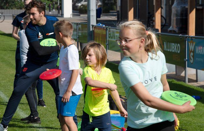 Buurtsportcoach Kevin van Olderen aan de slag met de kinderen in Kerk-Avezaath. Op de velden van Teisterbanders was het tijd om te frisbeeën.