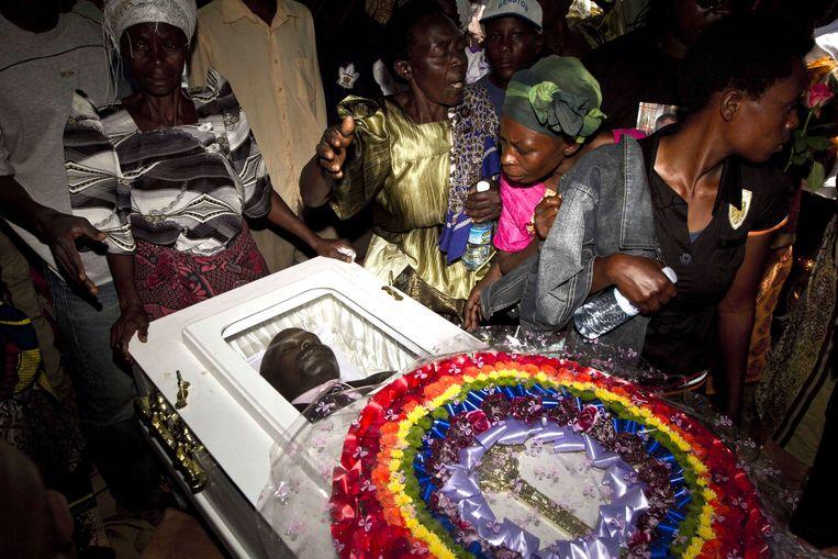 Leden van de Oegandese LGBT-gemeenschap rondom de doodskist van homoactivist David Kato, die in 2011 werd vermoord. Beeld afp
