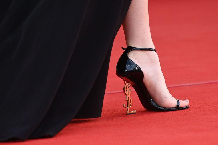 De hak van deze damesschoen bestaat uit de letters Y, S, L: de initialen van modeontwerper Yves Saint Laurent. De – onbekende – draagster van de schoen is deze week gefotografeerd op het Filmfestival van Venetië, waar zij de vertoning van de film Qui Rido lo ('De koning van de lach') bijwoonde. De film maakt kans op een Gouden Leeuw.  Beeld AFP