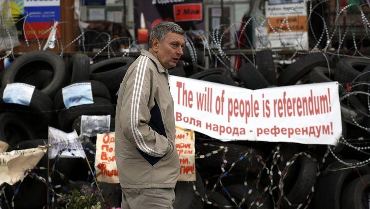 Een man loopt langs de barricades voor het bezette overheidsgebouw in Donetsk waar een spandoek hangt met de tekst 'de wil van de mensen is een referendum'.