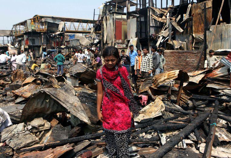 Rubina Ali bij het puin van haar huis na de brand. Beeld AP