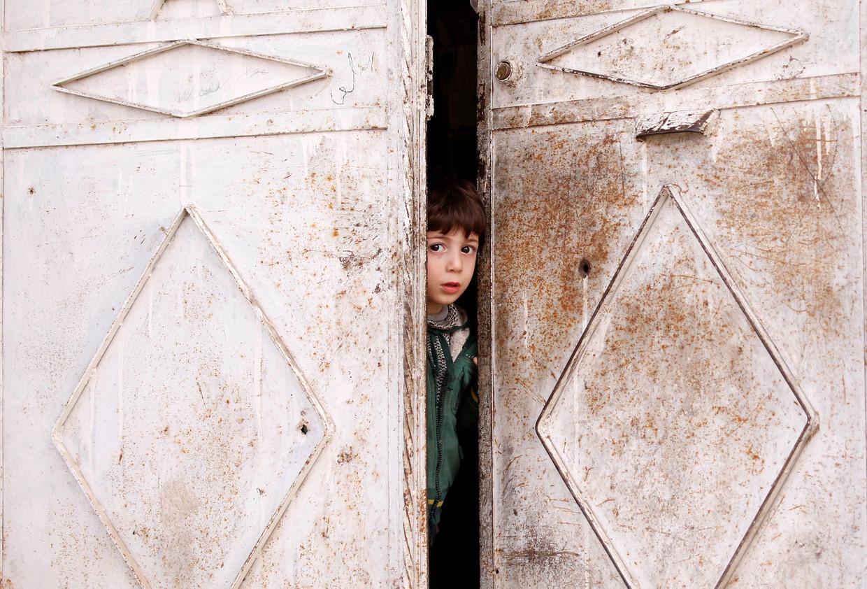 Een Syrisch jongetje kijkt naar buiten in Douma, in de oostelijke buitenwijken van Damascus.  Beeld REUTERS
