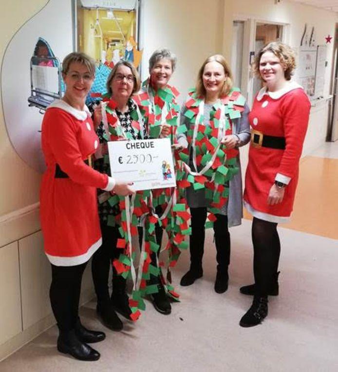 Evelien Koopman en Miranda van den Brink -van der Linde bieden de kinderafdeling van Gelre ziekenhuis in Apeldoorn een symbolische cheque aan. Daarnaast een lange slinger met persoonlijke wensen van leerlingen voor de kinderen op de kinderafdeling.