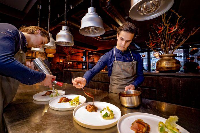 Chef-kok Thomas Vugts (rechts) werkt in zijn open keuken van restaurant Masz aan gerechten voor zijn gasten.