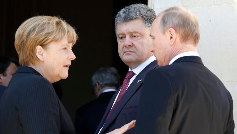 Merkel, Porosjenko en Poetin ontmoetten elkaar eerder dit jaar tijdens de D-Day-herdenking in Frankrijk. Beeld REUTERS