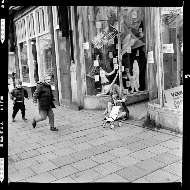 Kattenburg of Oostenburg, 1966. Twee kinderen hollen en rennen over de stoep. Een meisje voor een kledingwinkel met lingerie met een speelgoedkinderwagen. Beeld bert verhoeff