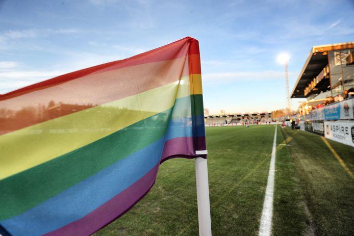 Een regenboogvlag langs een voetbalveld.