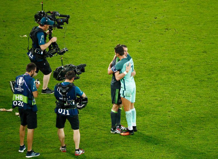 Eén van de mooiste momenten van het afgelopen EK: Ronaldo spreekt zijn maatje bij Real, Gareth Bale, troostende woorden toe na de halve finale Portugal-Wales. Beeld Photo News