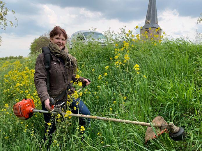 Marjan van Beest maait met haar bosmaaier het paadje naar de steiger bij de Linge even vrij in haar woonplaats Spijk.