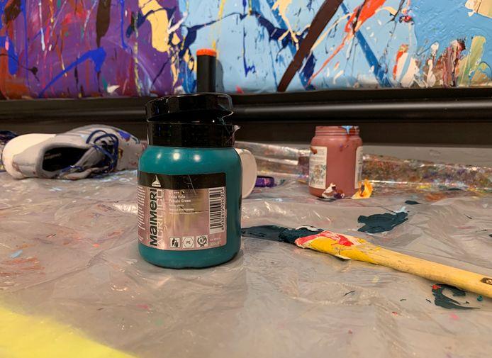 De verfpotten en kwasten maken onderdeel uit van het kunstwerk.