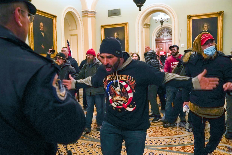 Trump-supporters staan oog in oog met de politie, aan de hal voor de Amerikaanse Senaat.  Beeld AP