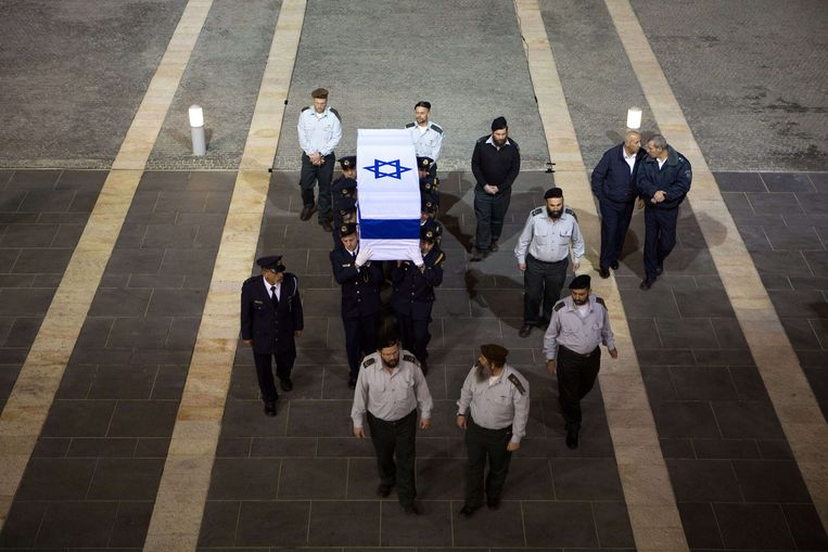 Israeli honour guards carry the coffin of former prime minister Ariel Sharon in to the Knesset (the Israeli Parliament) in Jerusalem at the end of the day on January 12, 2014 as Israelis came to pay their respects to Ariel Sharon, whose controversial life inspired admiration and provoked revulsion and whose death drew emotional reactions even after eight years in a coma. Celebrated as a military hero by some, recognised as a pragmatic politician by others and despised as a bloodthirsty criminal by his foes, Sharon was a polarising figure at home and abroad. AFP PHOTO/MENAHEM KAHANA Beeld AFP