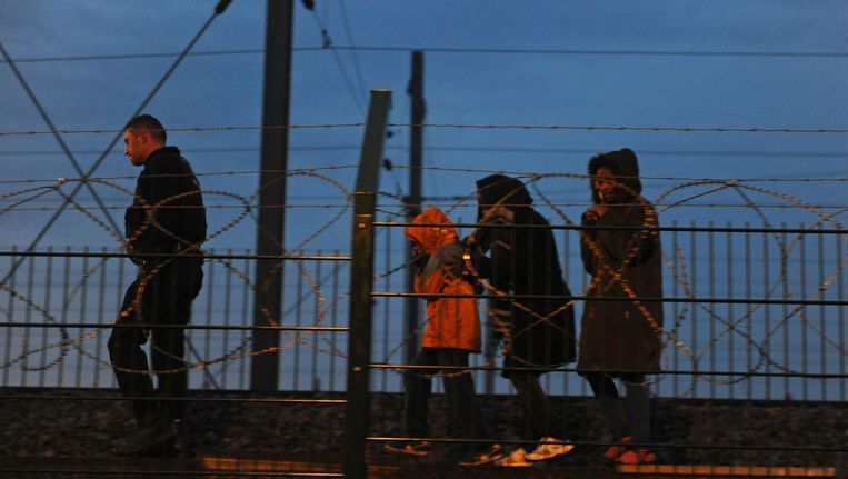 Vluchtelingen dwalen langs het spoor in Calais. Beeld AFP