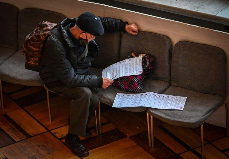 Een Moskoviet neemt de verkiezingsbiljetten door tijdens de eerste van de drie dagen durende parlementsverkiezingen. Beeld AFP