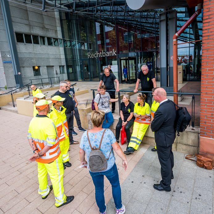 Verkeersregelaars voeren actie bij de rechtbank. Achter, met blauwe spijkerbroek, dochter Linda van de omgekomen Bert.