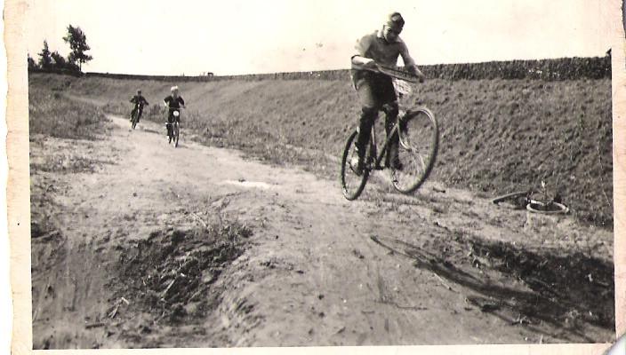 André den Edel zweeft over een heuveltje. Achter hem zijn broertje Frank