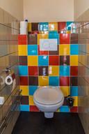 Ook de gekleurde wandtegels in de wachtkamer en het toilet verwijzen naar het verleden.