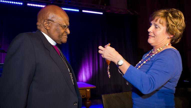Desmond Tutu krijgt de versierselen opgespeld door Ank Bijleveldd. Beeld anp