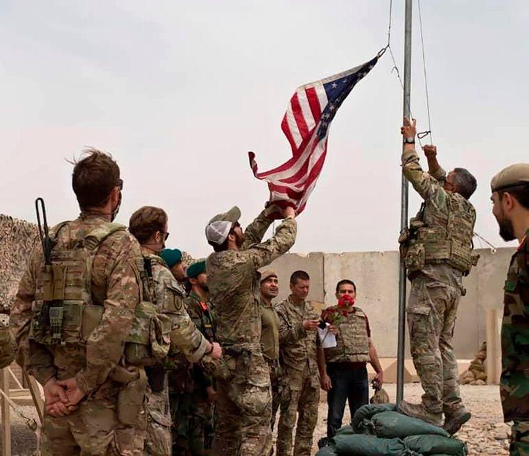 In Camp Antonic in Zuid-Afghanistan wordt de Amerikaanse vlag neergelaten bij de overdrachtsceremonie aan het Afghaanse leger, in mei 2021. Drie maanden later is zowat het hele land in handen van de taliban. Beeld AP