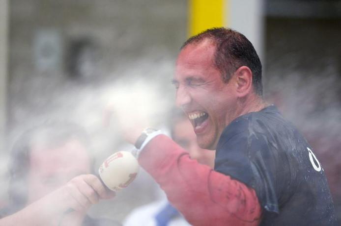 Nesselande-coach Ron Zwerver krijgt een champagnedouche na het behalen van de landstitel in Doetinchem terwijl hij de radioverslaggever te woord staat. foto Jan van den Brink