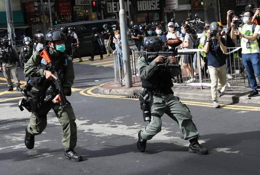 Leden van de oproerpolitie in Hongkong vuren balletjes vol pepperspray af op betogers.