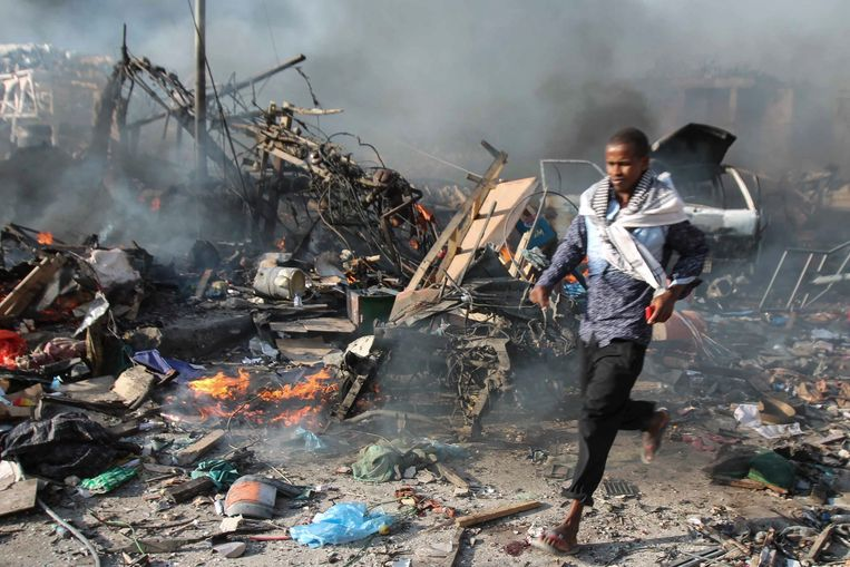 Een man loopt door het puin na een bomaanslag met een vrachtwagen voor het Safari Hotel in Mogadishu, op 14 oktober jongstleden. Beeld EPA