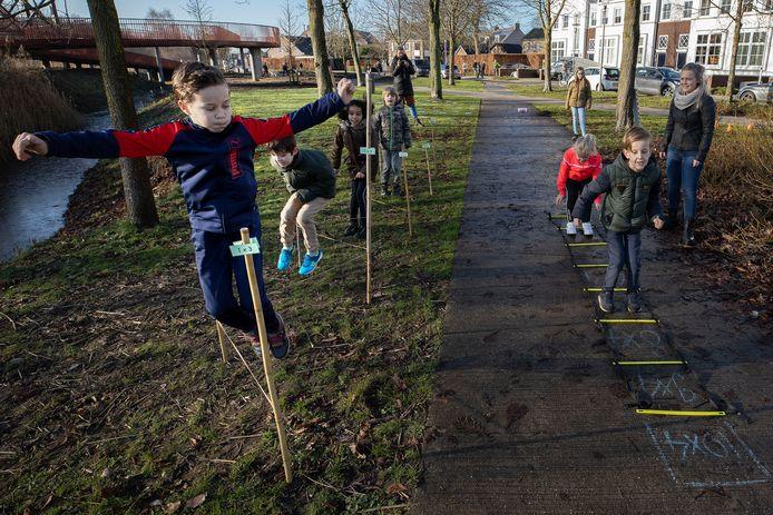 Jurre van Zwijndrecht (l) doet een tafeltjesoefening met het springtouw. Rechts kijkt juf Laura Beekmans goedkeurend toe.