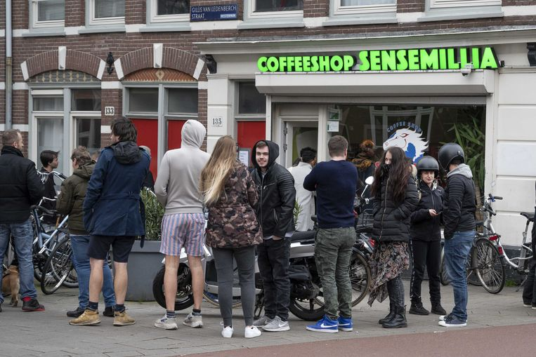 Drukte bij een coffeeshop waar klanten nog snel voor 6 uur een voorraadje in willen slaan voordat cafés en restaurants hun deuren sluiten.  Beeld ANP
