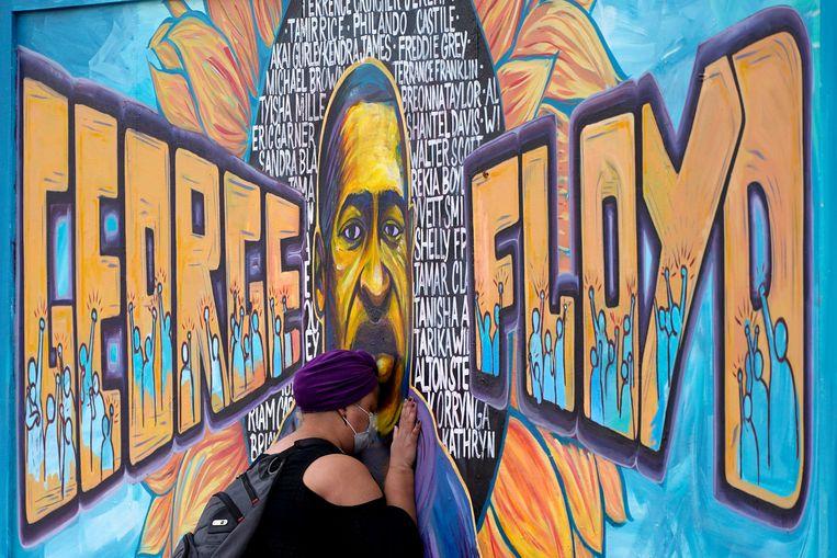 Een vrouw bij een muurschildering van George Floyd in Minneapolis.  Beeld AP