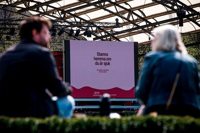 Een billboard waarop Zweden worden opgeroepen huis te blijven.