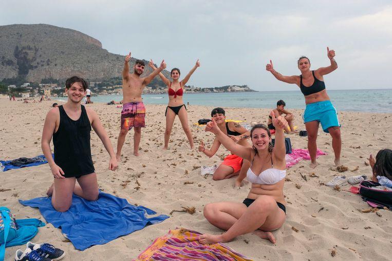 Badgasten vieren in mei 2020 de heropening van het Mondello-strand op Sicilië.  Beeld EPA