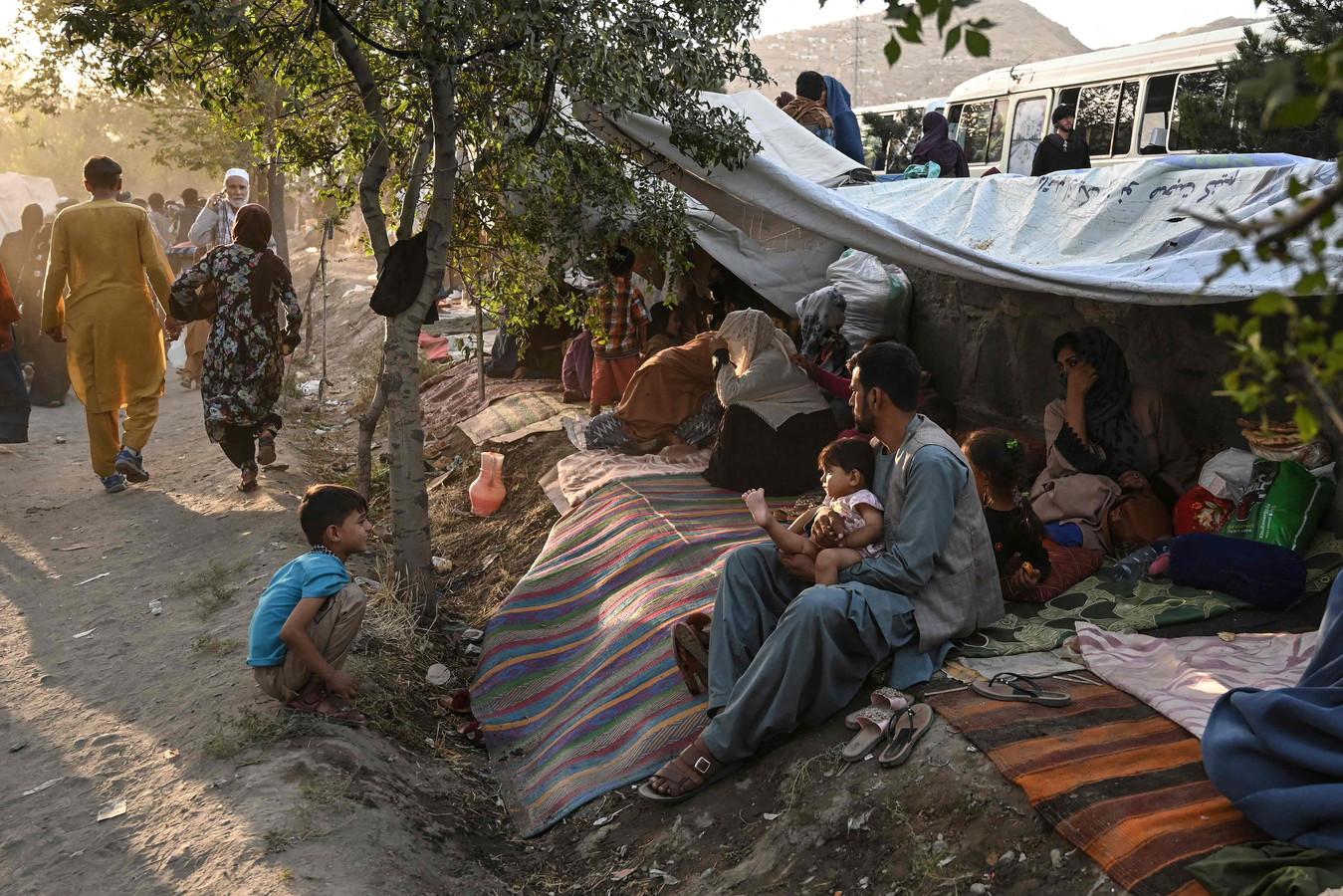 Afghaanse families die uit Kunduz zijn gevlucht, zitten voor hun tijdelijke tenten bij Sara-e-Shamali in Kaboel.
